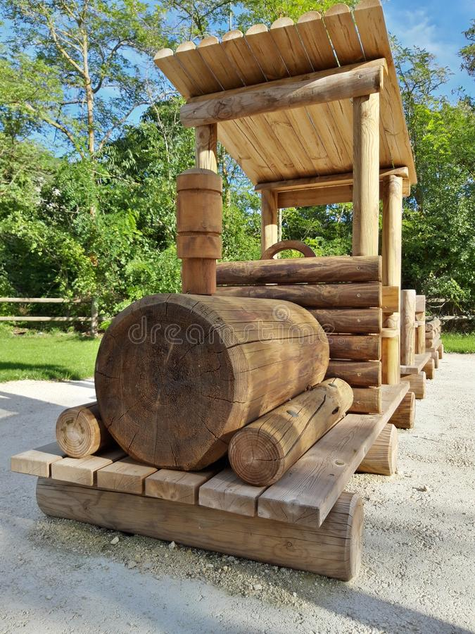 Wooden train on the playground for children.  Structure built by hand in the green of the mountains.  Image taken in Abruzzo. Wooden train on the playground for royalty free stock photography