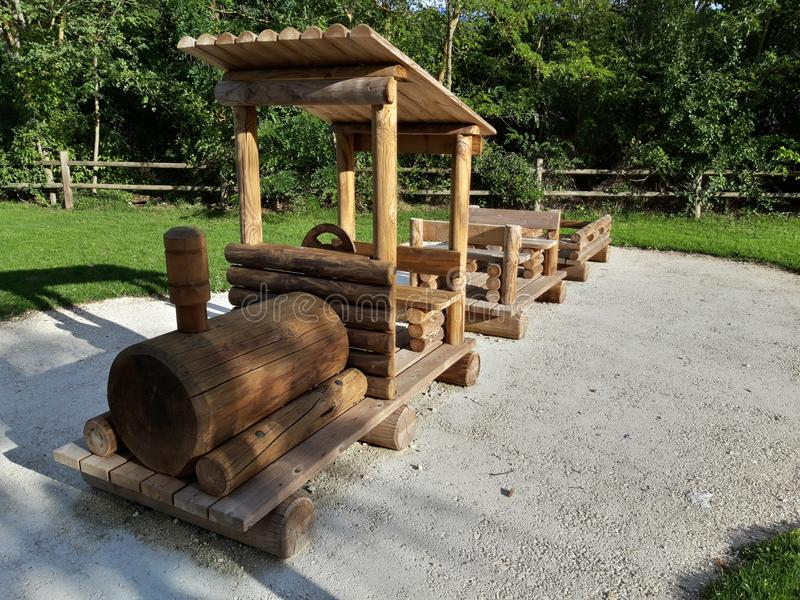 Wooden train on the playground for children.  Structure built by hand in the green of the mountains.  Image taken in Abruzzo. Wooden train on the playground for stock image