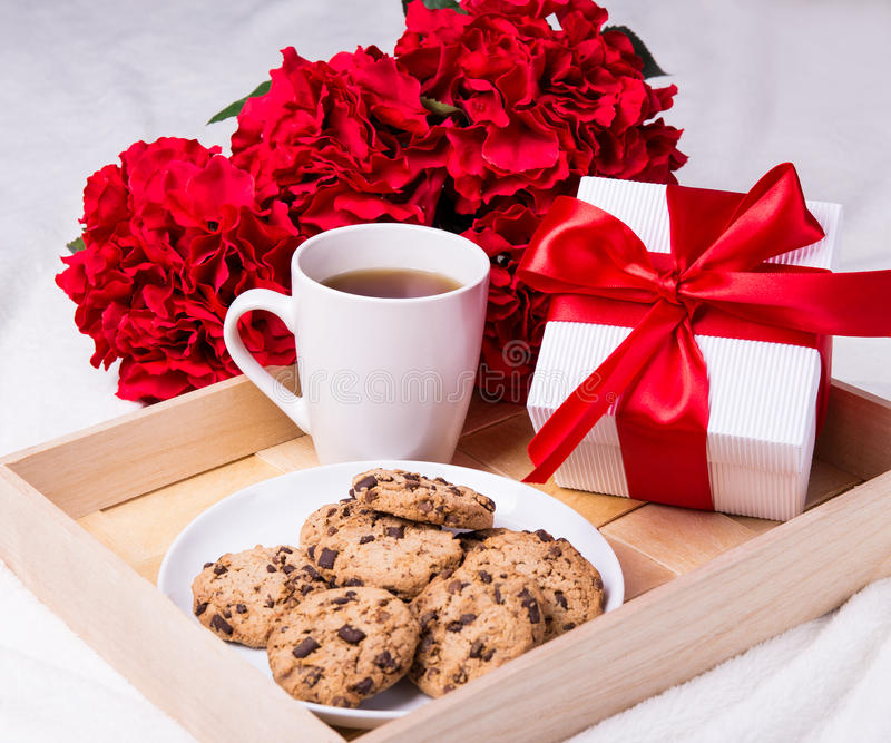 Wooden tray with chocolate chip cookies, cup of tea, flowers and. Close up of wooden tray with chocolate chip cookies, cup of tea, red flowers and gift box royalty free stock photography