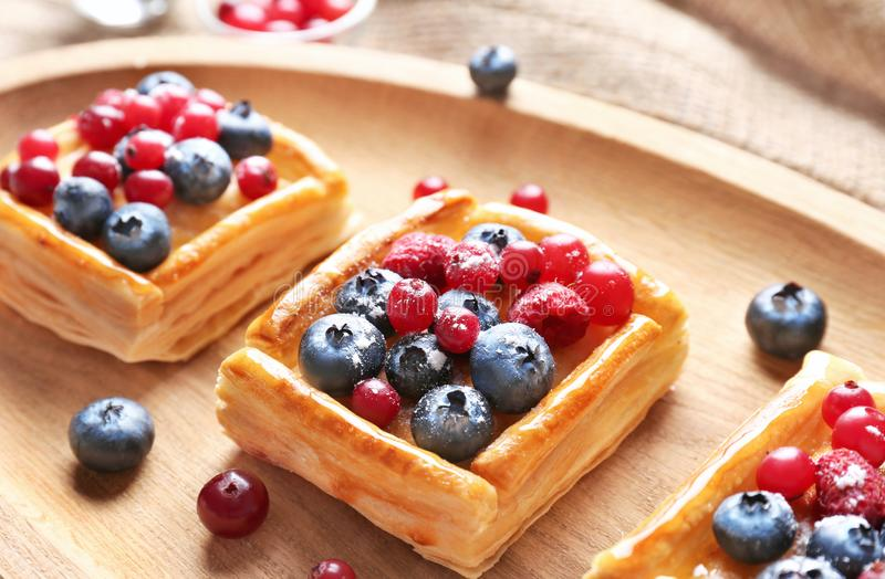 Wooden tray with delicious pastries. And berries, closeup stock photography