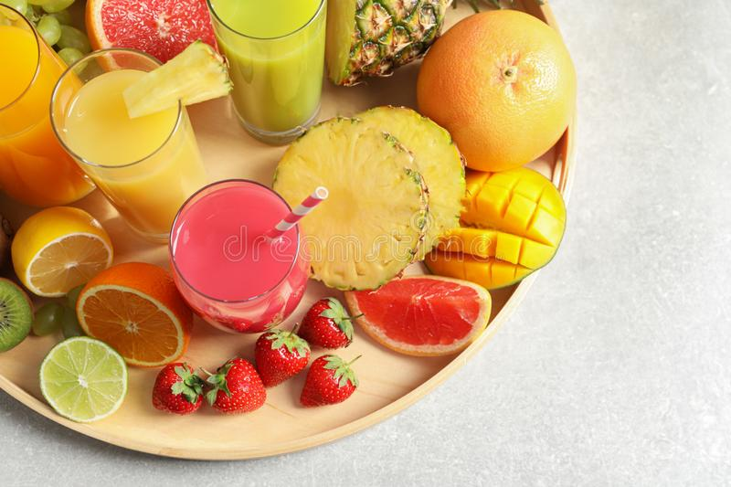 Wooden tray with glasses of different juices and fresh fruits on table, top view. Space for text stock image