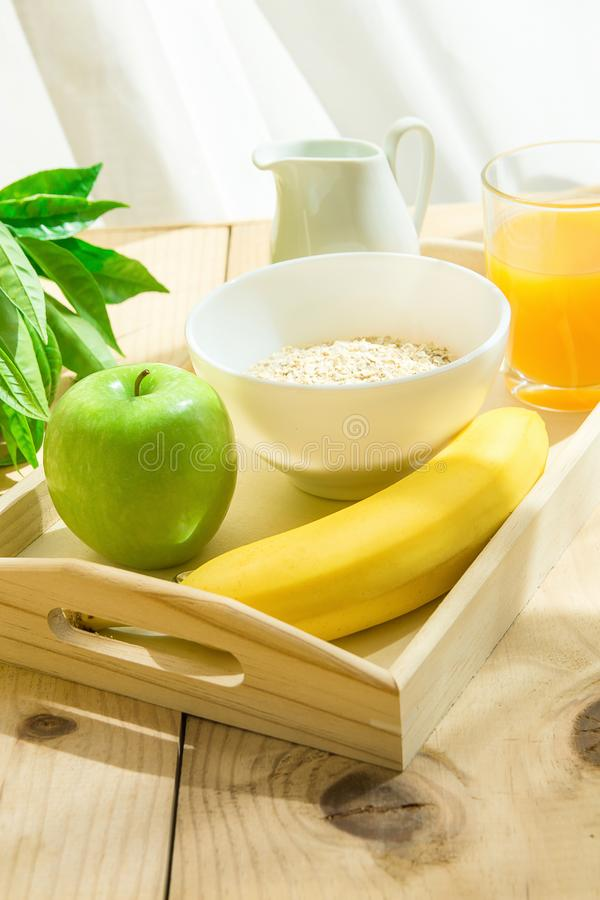 Wooden Tray with Healthy Breakfast Ingredients on Table. Oats in Bowl Nut Milk in Pitcher Orange Juice Banana Green Apple. Bright Morning Sunlight Streaming royalty free stock image