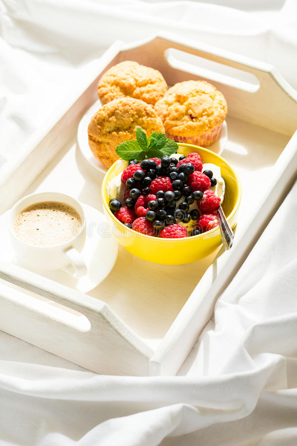 Wooden tray with tasty breakfast on bed. Espresso, banana muffins, cottage cheese with blueberry and raspberry royalty free stock photos