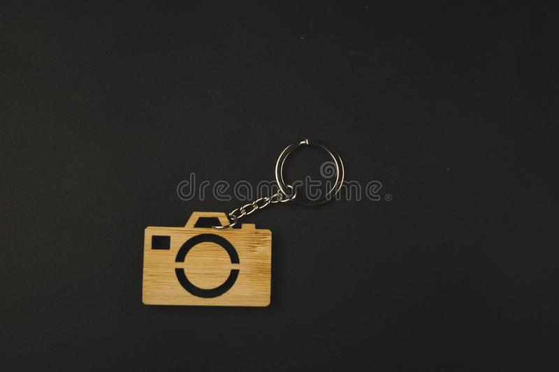 Wooden trinket in the form of a camera on a black background. keychain royalty free stock images