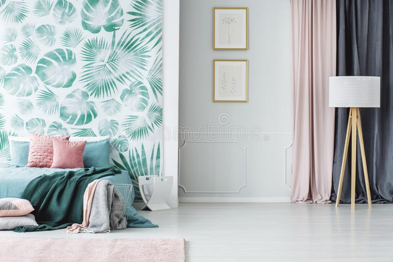 Cozy green and pink bedroom. Wooden tripod floor lamp and a big bed with pillows and blankets in a cozy pale green and pink bedroom interior royalty free stock photo