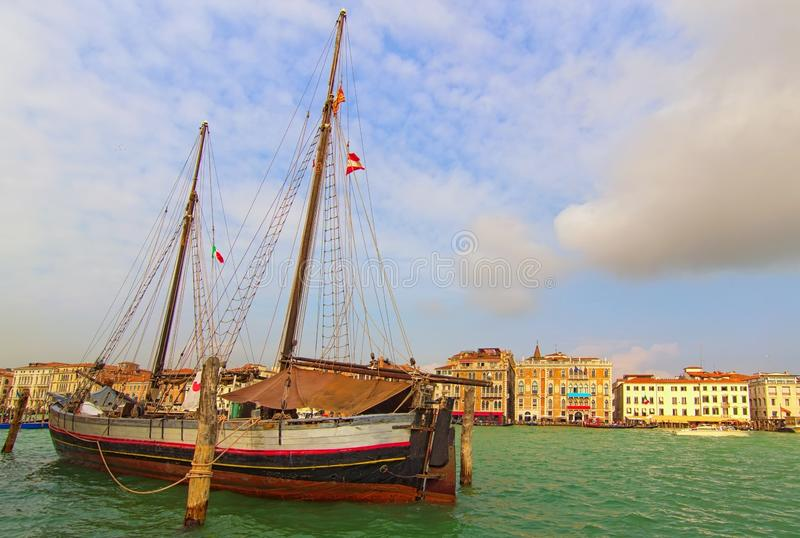 Wooden two-masted ship moored in Venice near Punta della Dogana. Ancient sailboat in open air on the canal quay stock photography