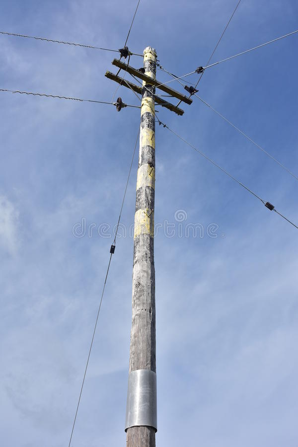 Wooden utility pole. Tall sun-bleached wooden utility pole with a few wires stock photos