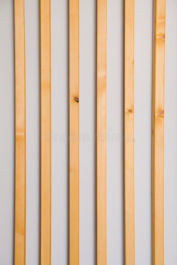 Wooden vertical slats batten on a light gray wall background. Interior detail, texture, background. The concept of minimalism and stock photography
