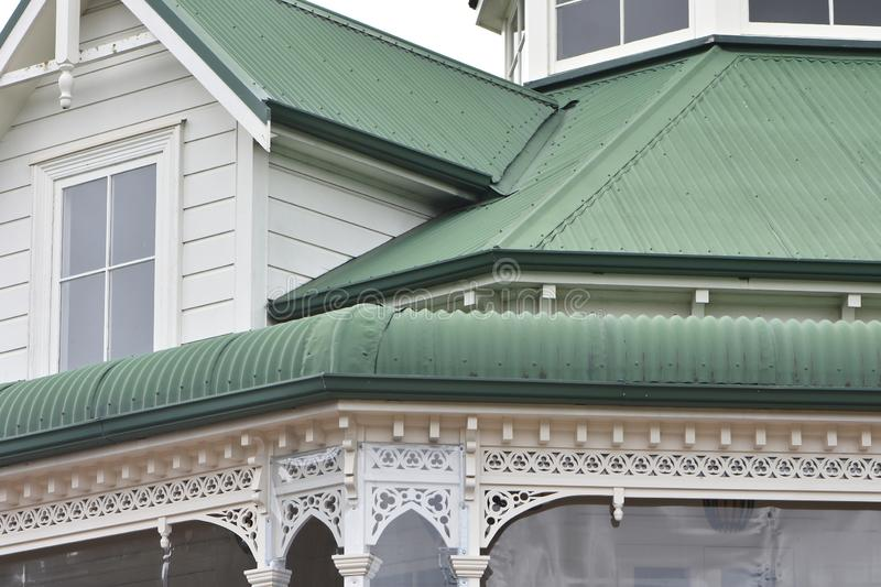 Wooden villa metal roofs. Detail of vintage white wooden villa with ornaments and corrugated sheet metal green painted roofs stock images