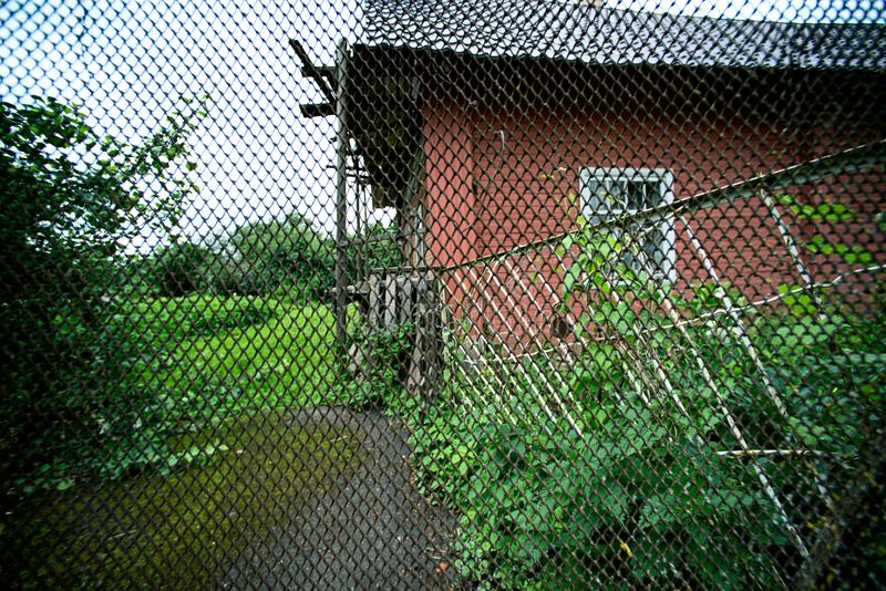 Village house through a metal grating fence. Wooden village house through a metal grating fence royalty free stock images