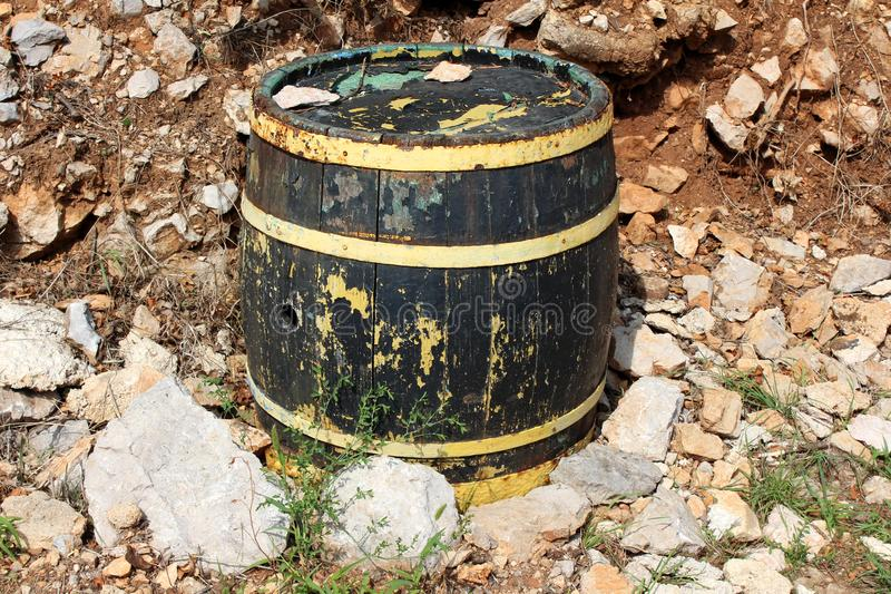 Wooden vine barrel with cracked boards and faded color left in backyard surrounded with stones and soil. On warm sunny day royalty free stock photos