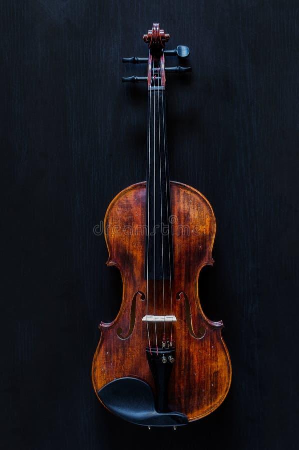 Wooden Vintage Classic Violin. Standard vintage violin made of wood on a black wooden surface stock image