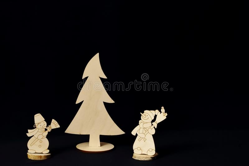 Wooden vintage figures of snowmen and spruce on black background in style of minimalism. Symbolic concept - Christmas, New Year, royalty free stock images
