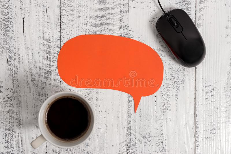 Wooden vintage table background black coffee cup wire mouse blank speech bubble. Empty text for promoting import events stock image