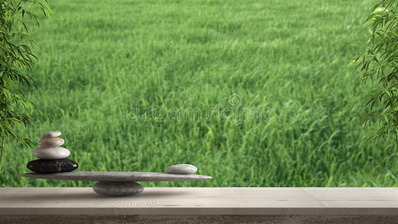 Wooden vintage table or shelf with stone balance, over blurred meadow panorama with green grass, feng shui, zen concept architectu royalty free stock images