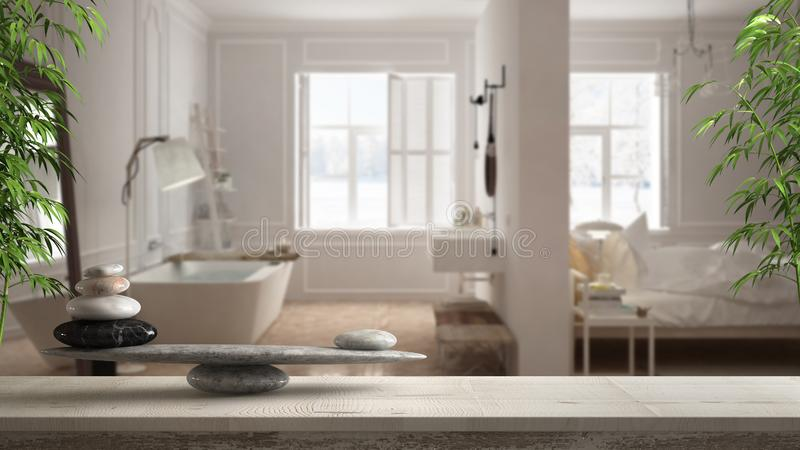 Wooden vintage table or shelf with stone balance, over blurred scandinavian bedroom and bathroom with panoramic window, feng shui, royalty free stock images