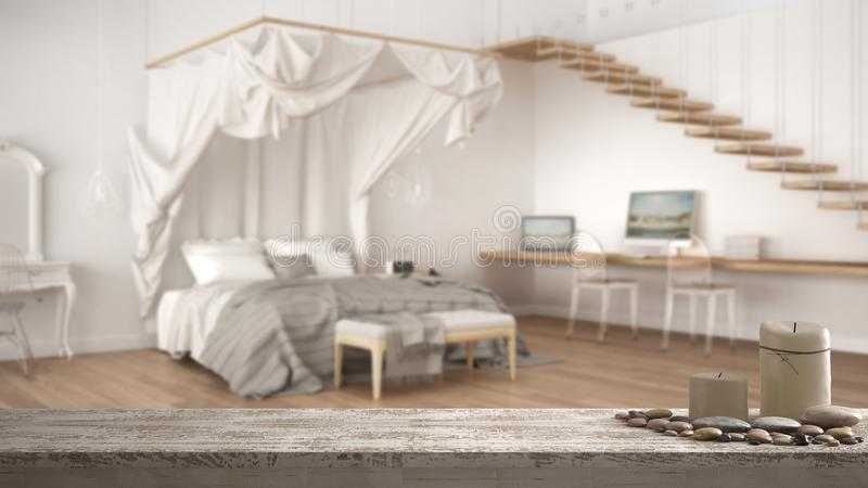 Wooden vintage table top or shelf with candles and pebbles, zen mood, over blurred classic bedroom with big canopy bed, white arch royalty free stock photos