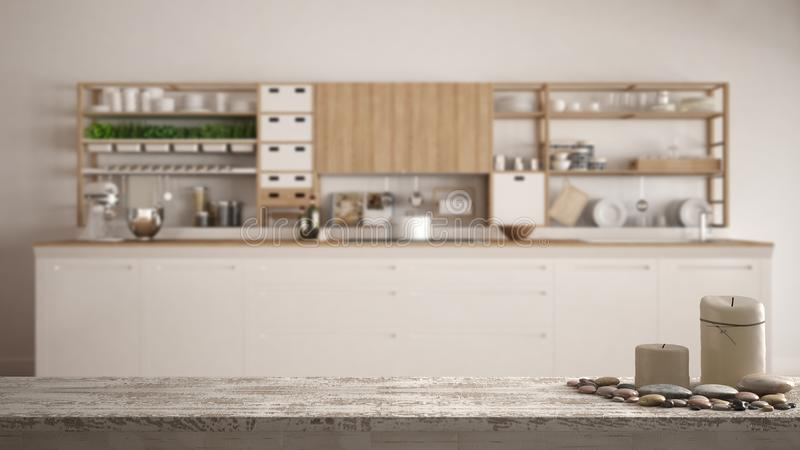 Wooden vintage table top or shelf with candles and pebbles, zen mood, over blurred empty minimalist white wooden kitchen closeup, stock photography