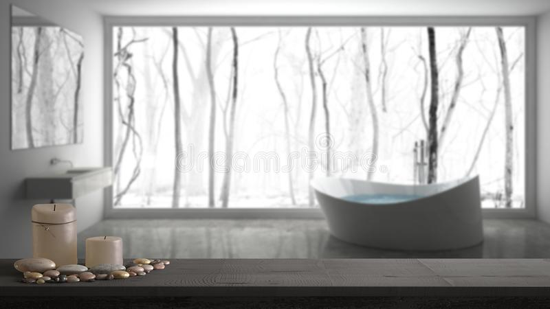 Wooden vintage table top or shelf with candles and pebbles, zen mood, over blurred gray bathroom with big panoramic window, white. Architecture interior design stock photo