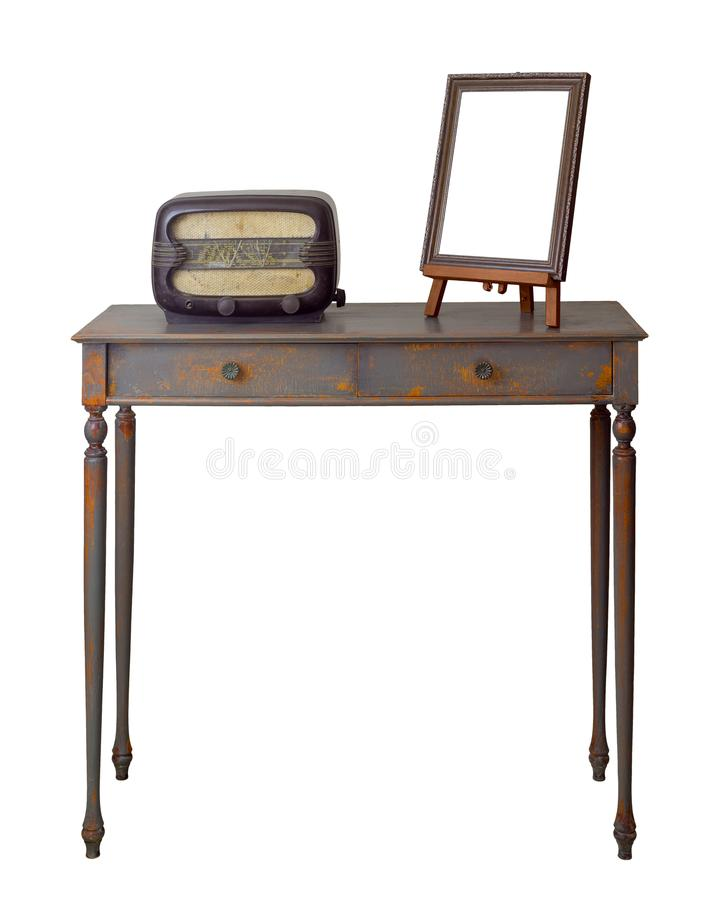 Wooden vintage table with two drawers painted in grey and orange, wooden ornate brown desktop photo frame and old radio stock image