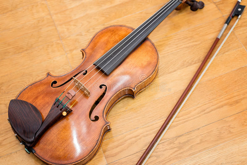 Wooden violin. With its fiddlestick royalty free stock image