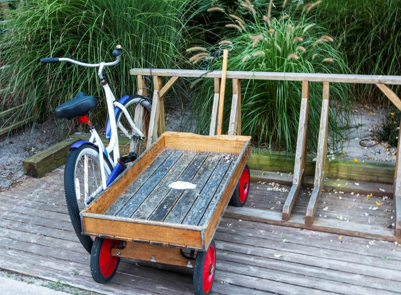Wooden wagon and cruiser bike on Fire Island. A cruiser bicycle and a wooden wagan are parked in a wooden bike rack in front of a summer home in Fire Island Long stock photos