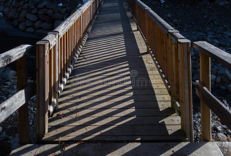 Wooden walking bridge crossing river canyon. Bridge of wood crossing a river canyon in the Alps with strong shadows from afternoon sunlight royalty free stock images