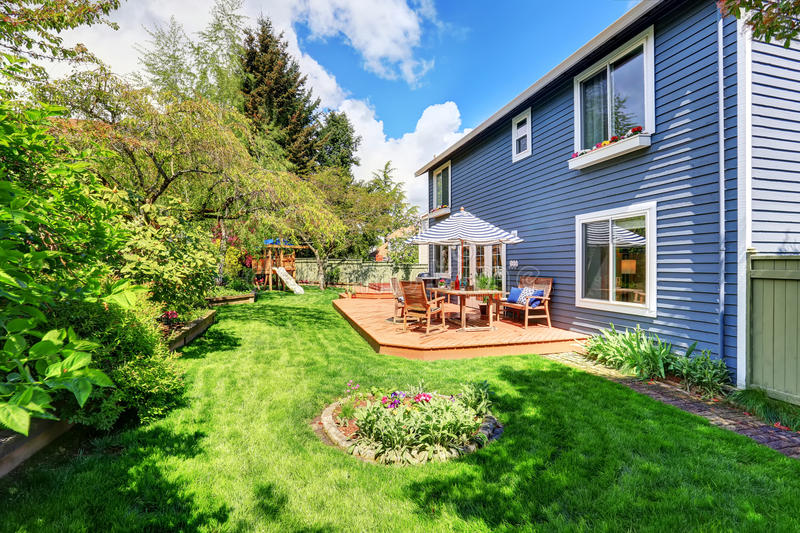 Wooden walkout deck in the backyard garden of blue siding house. Furnished with patio table set with umbrella royalty free stock images