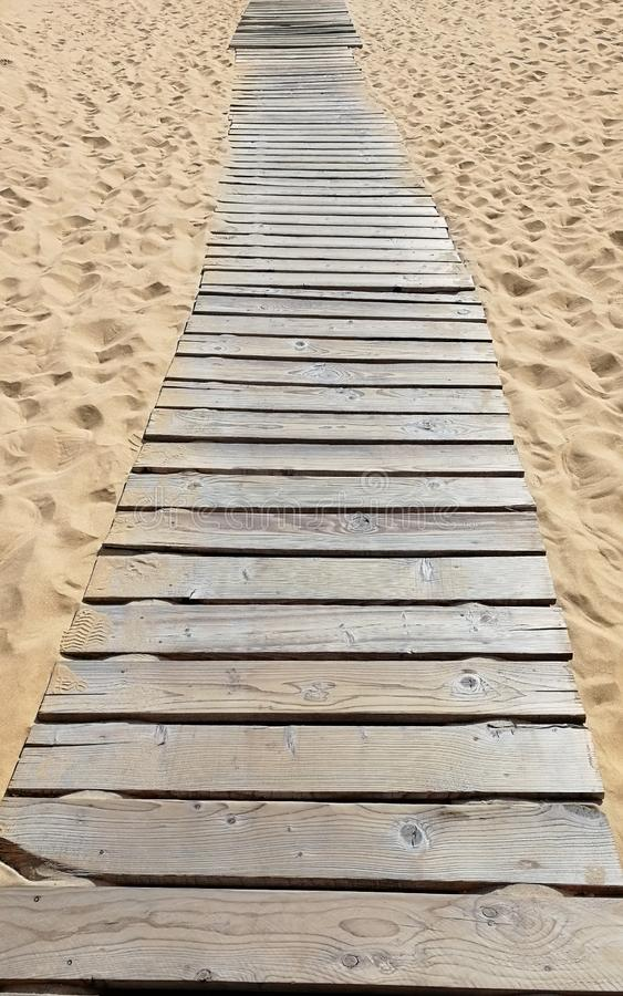 Wooden walkway on the beach. Summer pedestrian road on the sand royalty free stock images