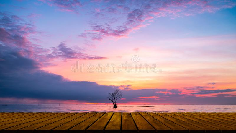 Wooden walkway with lonely tree in lake  and colorful sky at Pak pra village. Phatthalung, Thailand royalty free stock photos