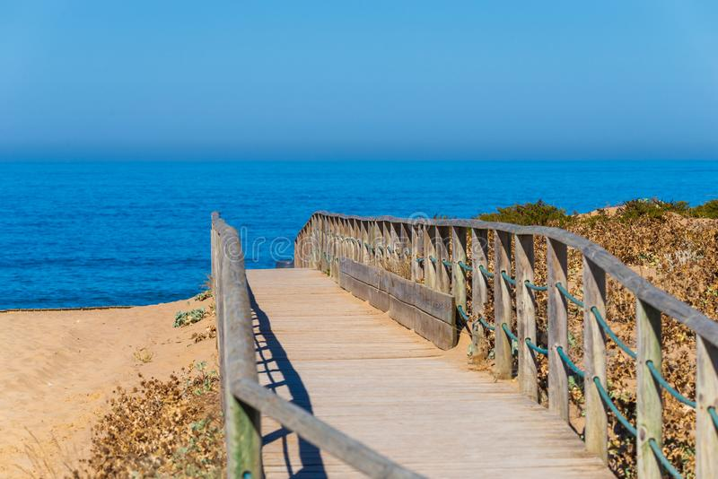Wooden walkway or path on a beach. Sea, blue, nature, ocean, water, rail, over, seaside, boardwalk, coast, footpath, sand, vacation, cadiz, horizon, dune stock image
