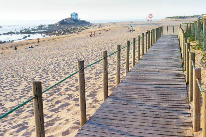 Wooden walkway, people, beach, church. Wooden walkway, people at sandy beach in evening sunlight, Senhor da Pedra church in background by seashore, Porto stock image