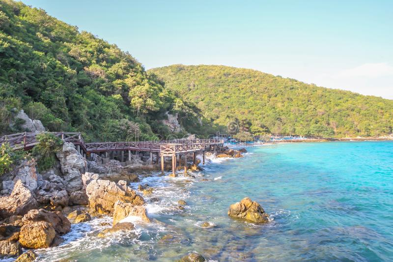 Wooden Walkway , Rocky coast and mountain with blue sea on KohLarn , Chonburi, Thailand. Wooden Walkway , Rocky coast and mountain with blue sea and blue sky on stock photo