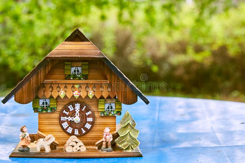 Wooden wall clock in the form of a house stand on a blue surface. Background - bright green bushes. royalty free stock image