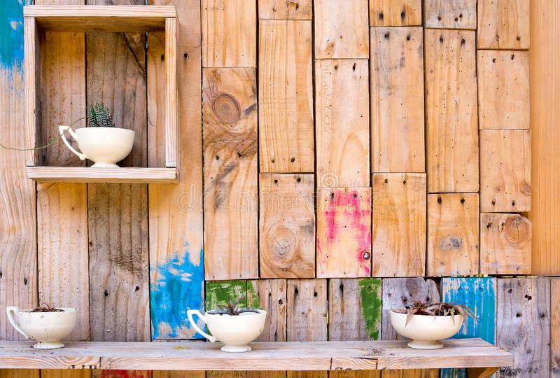 Wooden wall decoration with shelves and vases cup with flowers stock photo