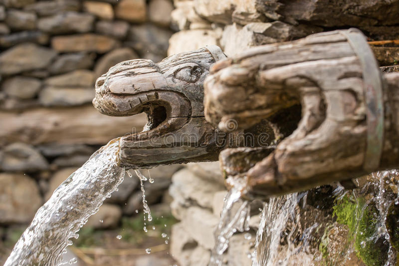 Wooden wall fountain in nepalese village in Annapurna Region. Nepal royalty free stock photography