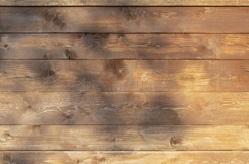 Wooden wall of horizontal brown boards with soft shadows in the evening sun as background royalty free stock photos