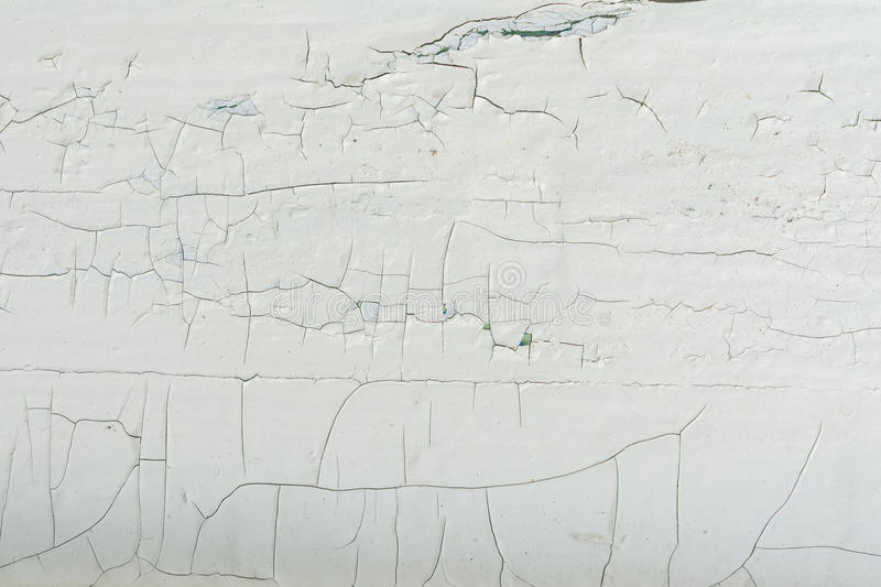 Wooden wall with white paint is severely weathered and peeling. Wooden wall with white paint is severely cracked and peeling, abstract background royalty free stock photo