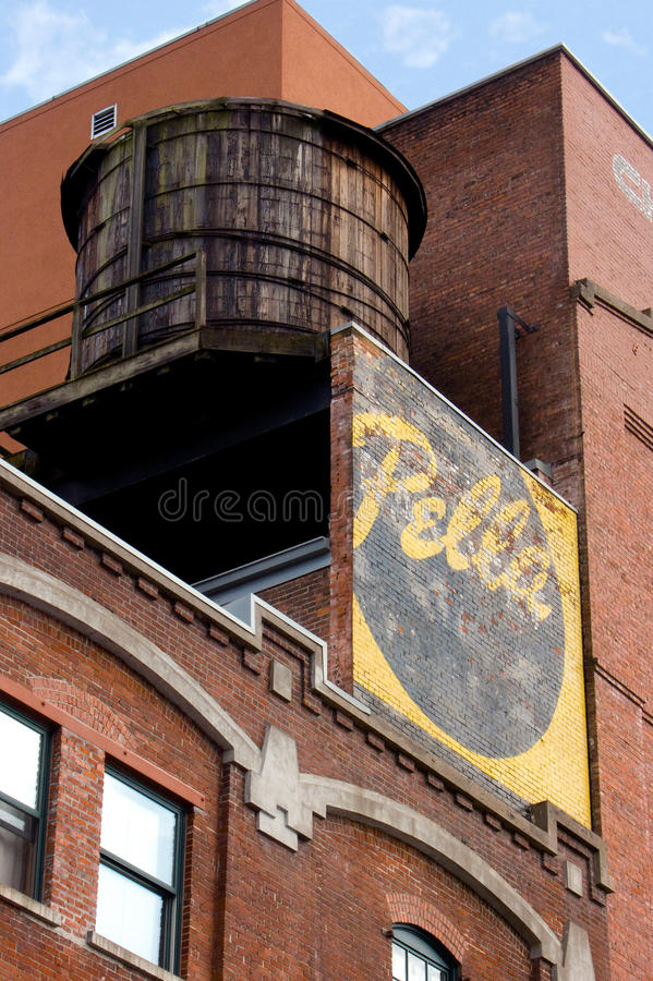 Wooden Water Tank on Brick Building. With Pella sign. Photographed in Portland, Oregon royalty free stock photos