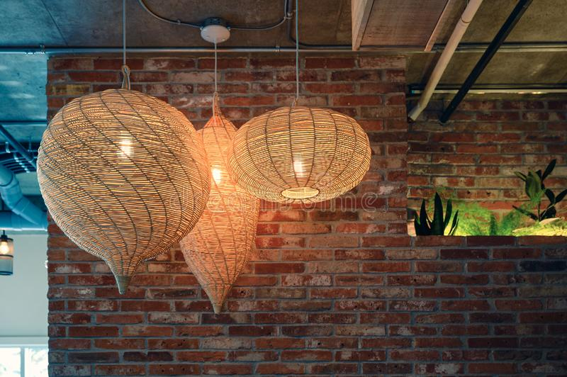 Wooden weave lamp hanging on ceiling and brick wall stock images