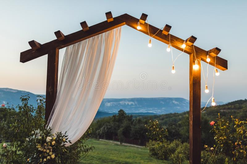 Wooden night wedding arch with light bulbs outdoor royalty free stock photos