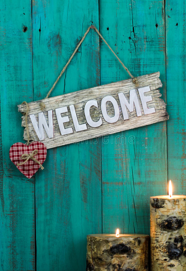 Wooden welcome sign with red heart and burning candles hanging on antique teal blue weathered fence стоковое изображение rf