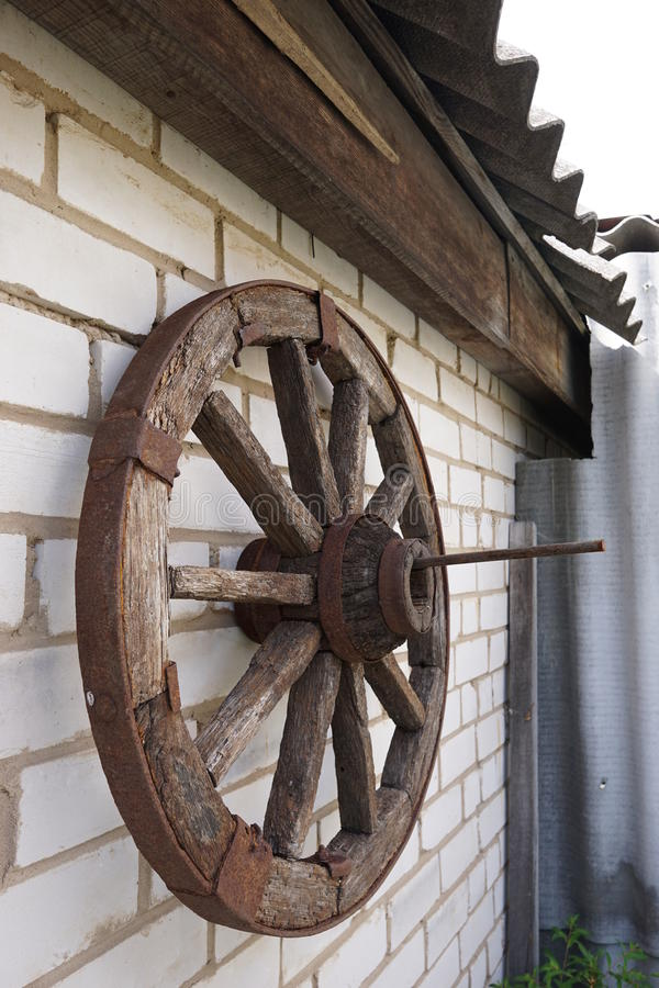 Wooden wheel on a background of green grass. Wooden wheel is on a green grass stock images