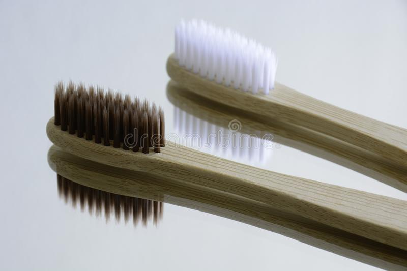 Wooden white and brown toothbrushes on mirror. stock photo
