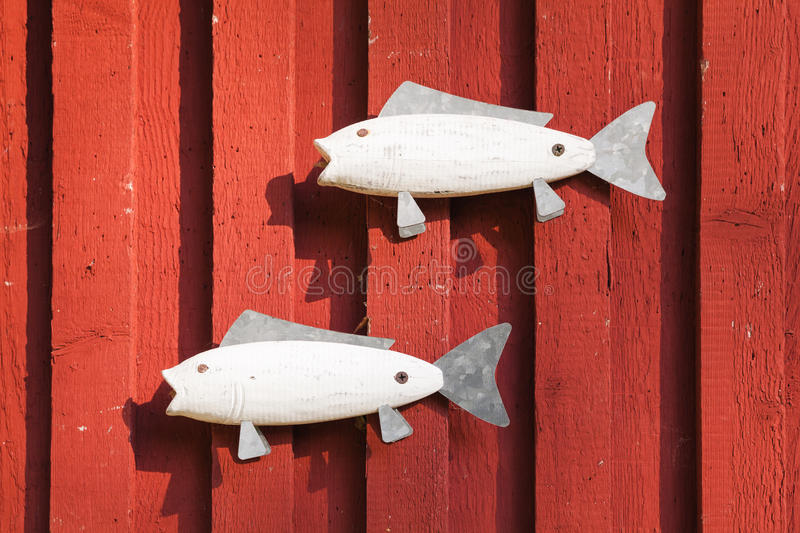 Wooden white fishes on red house wall stock photo