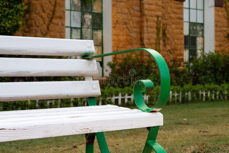 Wooden white garden bench with blurred background of orange bricks wall with windows stock photo