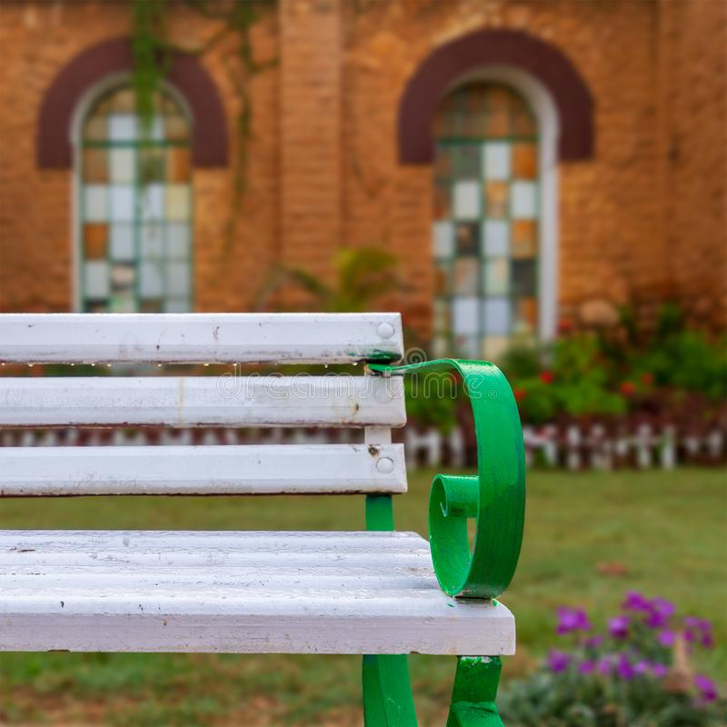 Wooden white garden bench with blurred background of orange wall with two huge windows in a public park royalty free stock photography