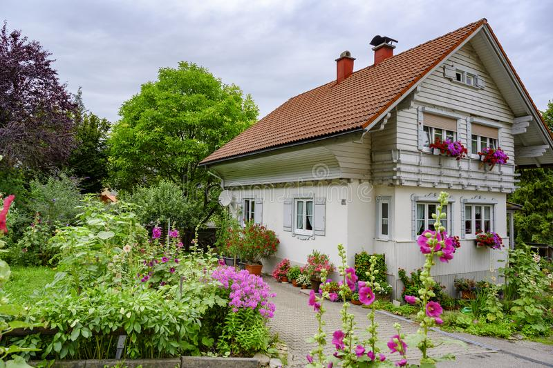 Wooden white house in Alps with beautiful flowering summer garden stock photos
