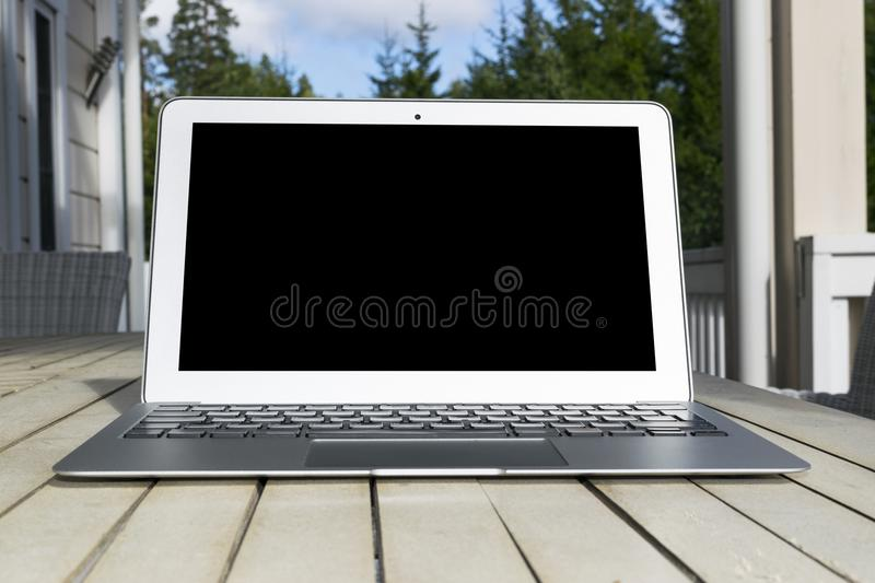 Wooden white office desk table with open blank laptop computer empty space. Front view with copy space. Grey laptop on wooden desk royalty free stock images