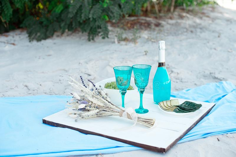 Wooden white picnic table with a bottle of blue champagne and plates with different cheeses, concept for a seasonal. Outdoor or holiday party or picnic royalty free stock photography